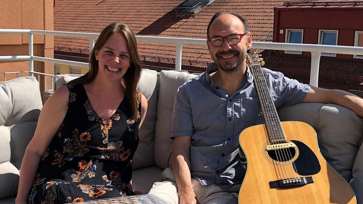 En man och en kvinna sitter i en soffa på en uteplats. Mannen håller i en gitarr.