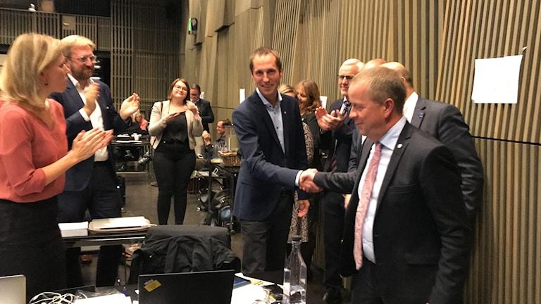 Fredrik Ahlstedt (M) skakar hand med Erik Pelling (S) efter att den senare valts till kommunstyrelsens ordförande.