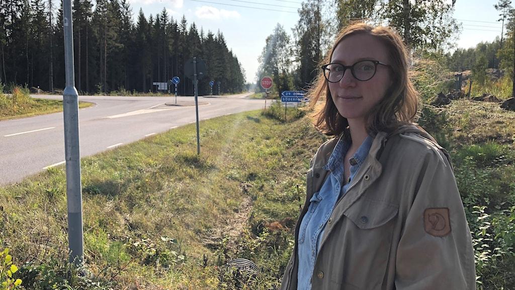 Kvinna står till höger i bild, till vänster och i bakgrunden syns en bilväg och korsning.
