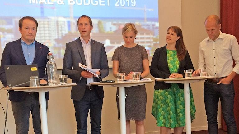 Kommunalpolitiker står vid ett podium och presenterar årsbudgeten