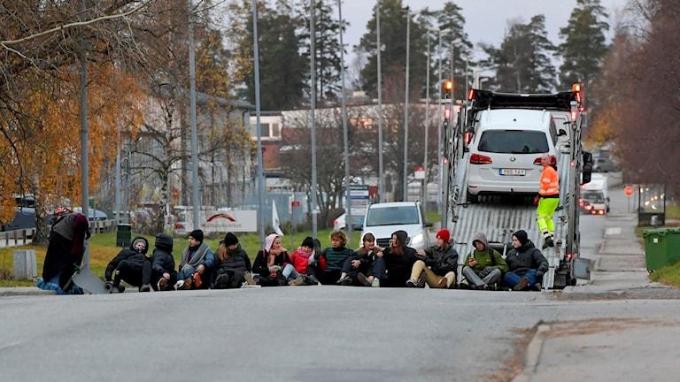 Aktivister sitter på gatan för att blockera utfarten från Migrationsverkets lokaler i Märsta