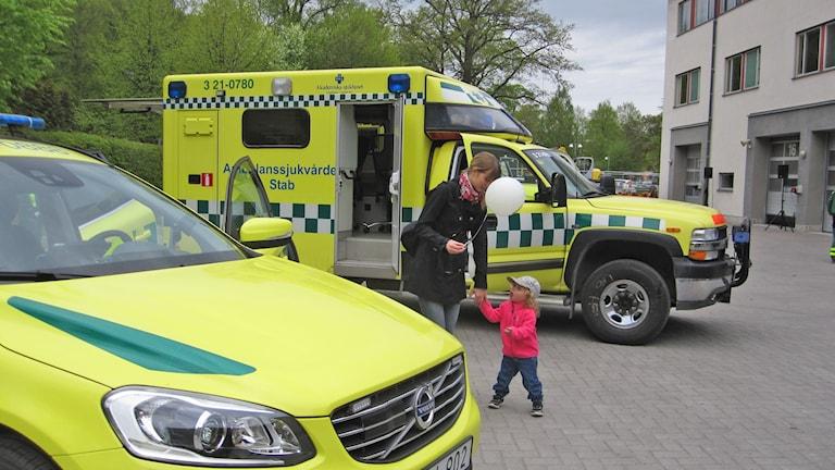 Barn och vuxen står vid ambulanser.
