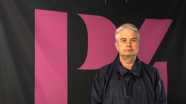 En man står framför en svart vägg med en rosa P4 logga på.