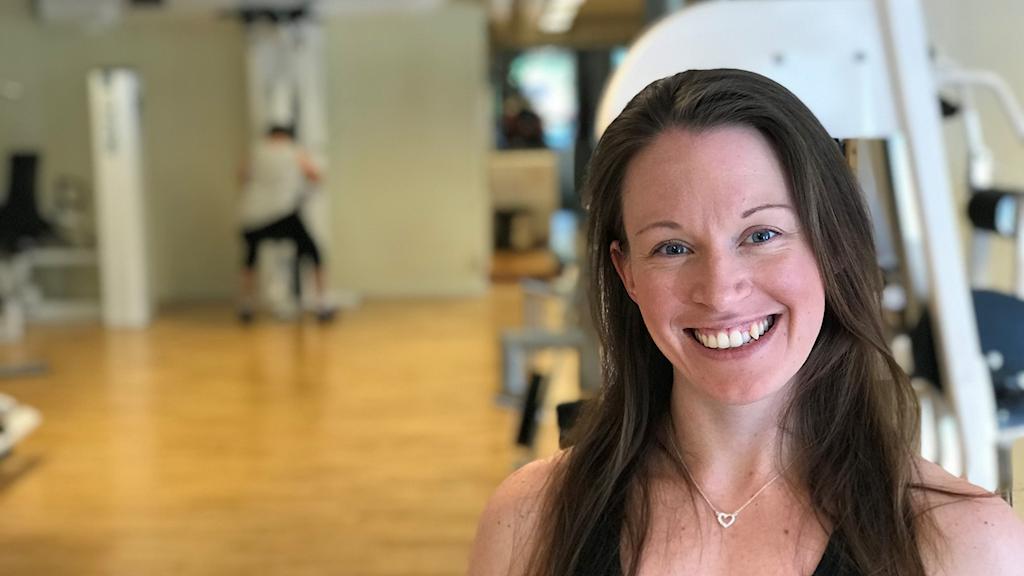 Jenny syns till höger i bilden med ett stort leende och i bakgrunden syns en av dem som kommer till hennes gym i Enköping och tränar.