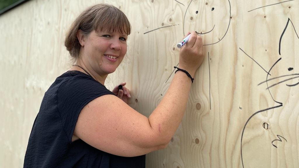 Kvinna står framför en plywoodvägg och målar en sol.