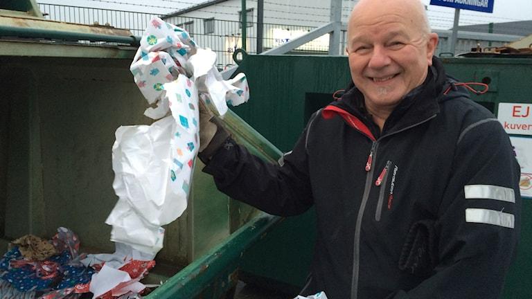 Man slänger julpapper på återvinningscentral.