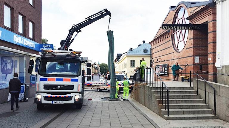 En kranbil som plockar bort konstverket Vriden Pelare av Sivert Lindblom utanför Stadsbiblioteket i Uppsala.