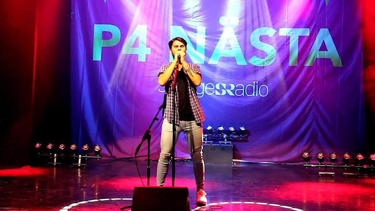 Ung man i jeans och skjorta håller båda händerna på en mikrofon på ett stativ och sjunger.