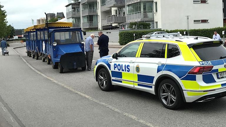Ett blått turisttåg stoppas av en polisbil.