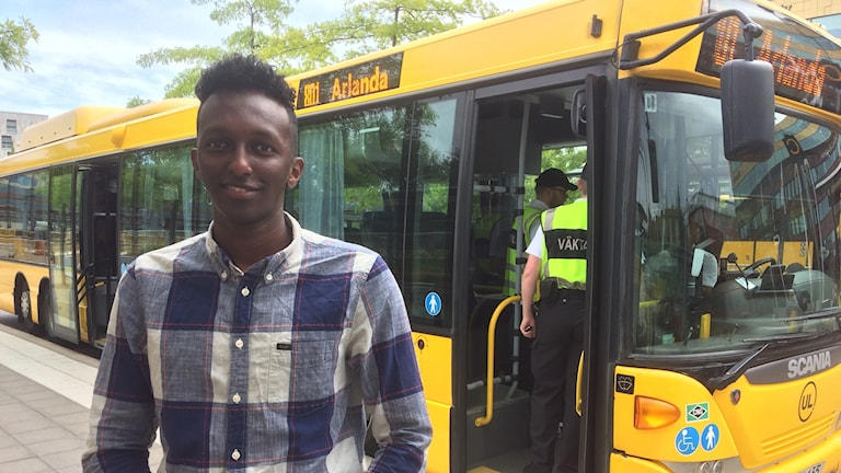 En man står framför en gul stadsbuss och tittar in i kameran.