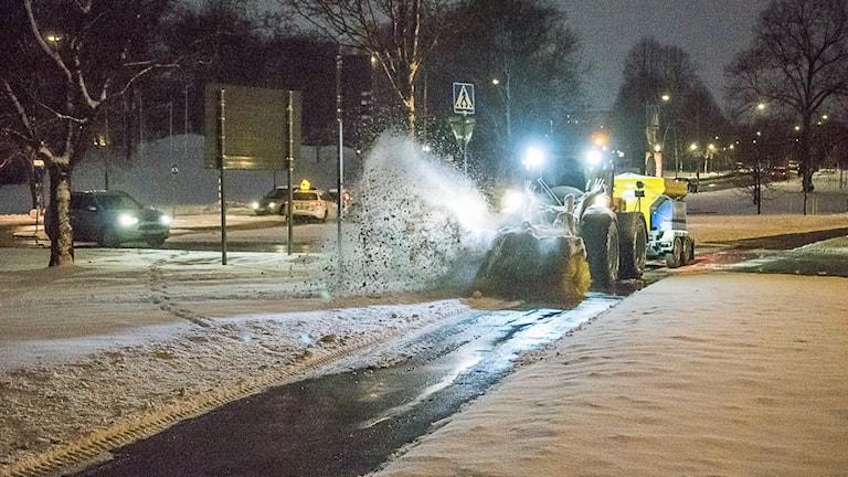 Snöröjningsmaskin med tända lyktor sprutar snö.