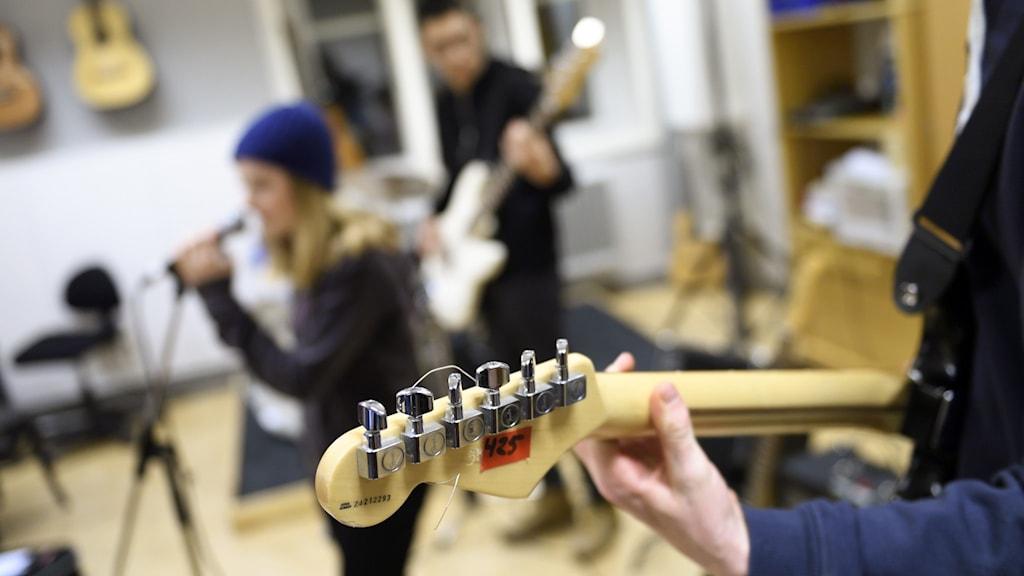 Ungdomar spelar elgitarr och står vid mikrofonstativ i en musiklokal.
