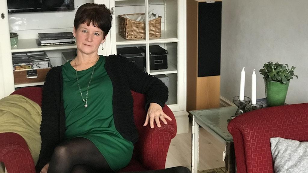 Anna-Karin Hall sitter i en röd, begagnad fåtölj bredvid sitt egendesignade sidobord, gjort av gamla fönsterramar och gammalt återvunnet glas.
