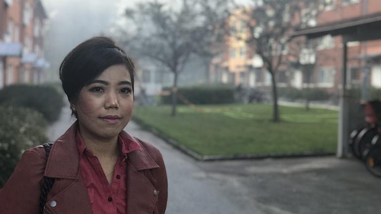 Kvinna står utanför lägenhetshus, brandrök i bakgrunden.