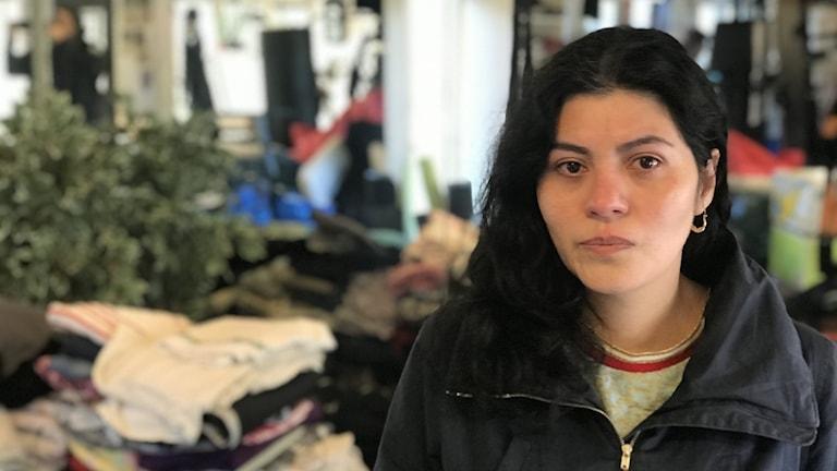 Kvinna med ledsen uppsyn står framför ett bord med kläder.
