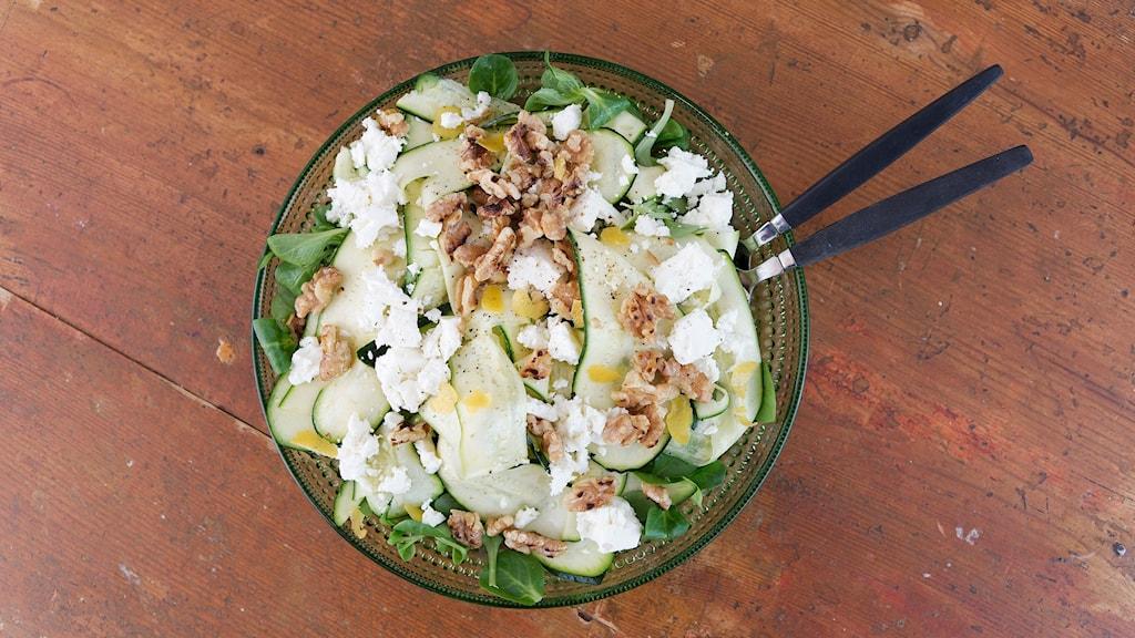En grön flat tallrik är fylld med ingredienserna till salladen. Ett par salladsbestick sticker ut på höger sida och det brunröda matbordet ramar in bilden som bakgrund.