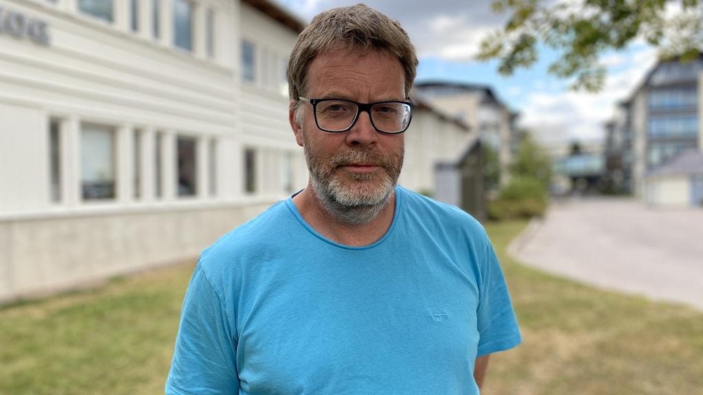 En man med grått hår och skägg, svarta glasögon och en ljusblå t-shirt står framför en vit byggnad.