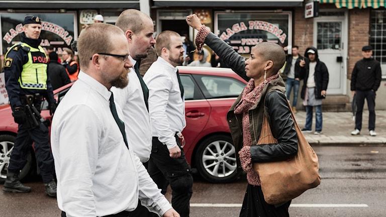 Tess Asplund står emot nazister under demostration.