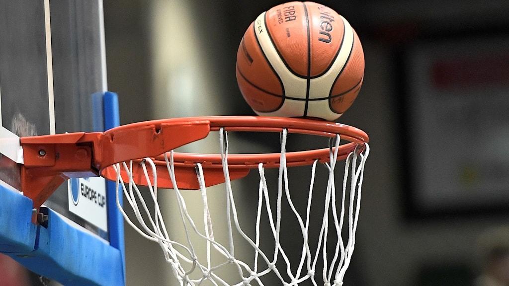 Basketboll träffar korgen. Genrebild.