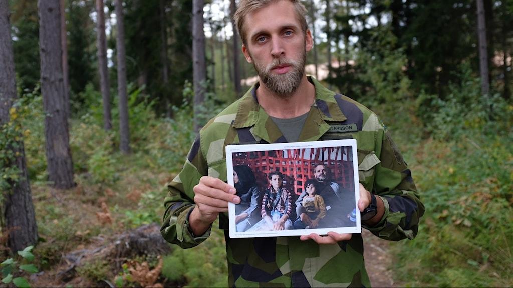 En fotograf i militärkläder håller upp ett foto.