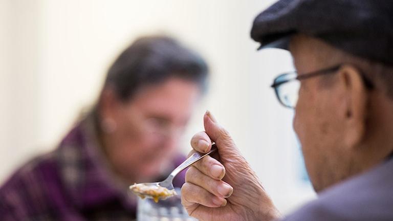 en äldre person sitter och äter