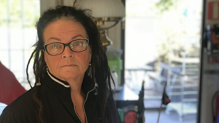 Kvinna med glasögon och dreadlocks står i ett rum.