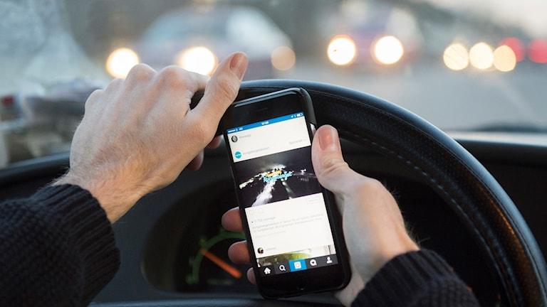 Bilist med mobil i handen (arkivbild).