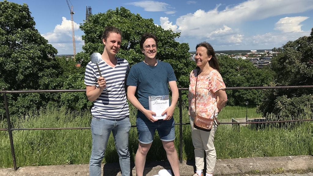 Felix står med en slev i handen, Hannes står och håller en gammal vinbox med folié på och bredvid står Karin.
