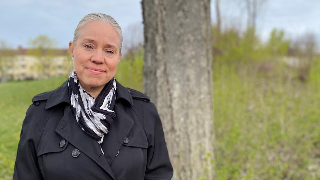 En kvinna står vid ett träd.