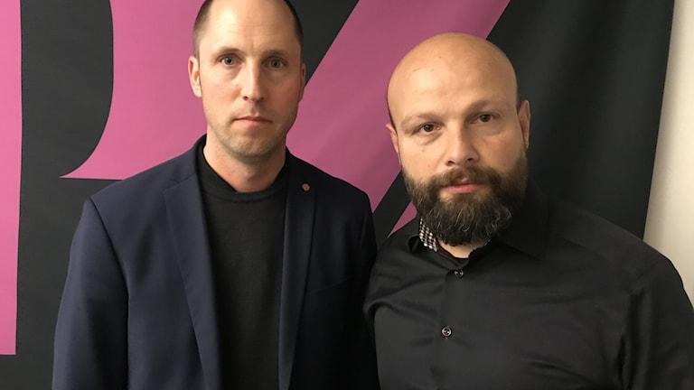 Till höger en man med svart skägg och svart skjorta. Till vänster en man med kort mörkt hår och svart kavaj.