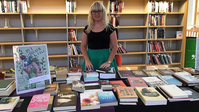 Emelie Kellnberger står bakom ett bord med böcker på Uppslaa stadsbibliotek.