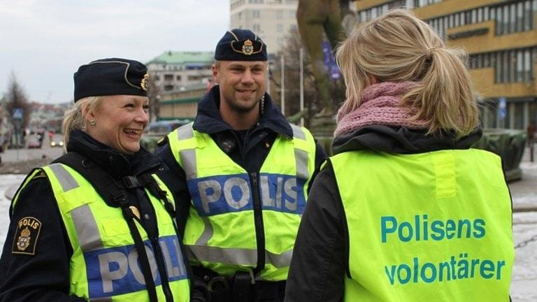 Två glada poliser står och skrattar med en volontär.