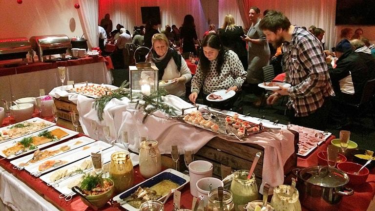 Julbord, tre personer står och böjer sig över bordet och plockar mat.