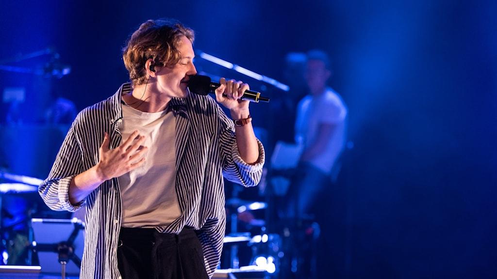 Den unga artisten Elias O uppträder under Riksfinalen av P4 Nästa 2021 i Västerås. Elias har page, ljus t-shirt, mörka byxor oc hen stor svartvit skjorta på sig. Han står på en scen i blått ljus, i bakgrunden anas musiker.