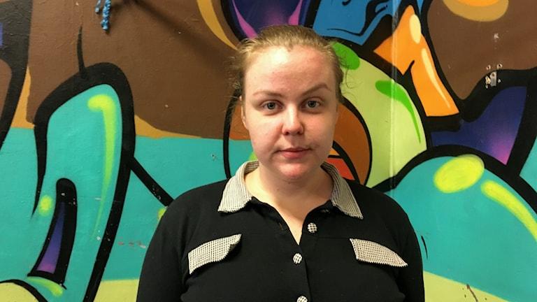 Agnes Öbergs, 23 från Ungdomes Hus står framför en grafittivägg