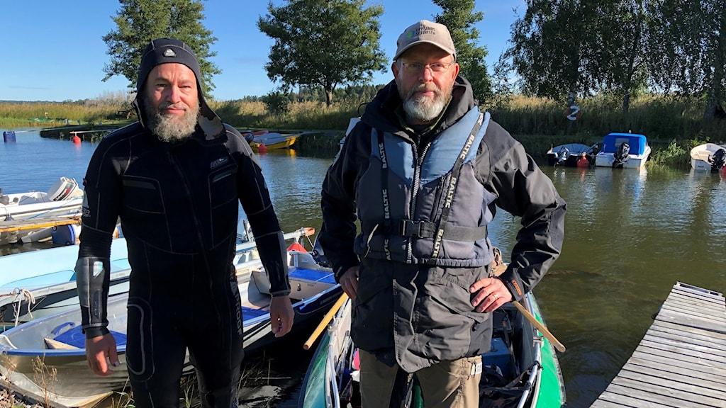 Två män står vid en fiskebrygga.