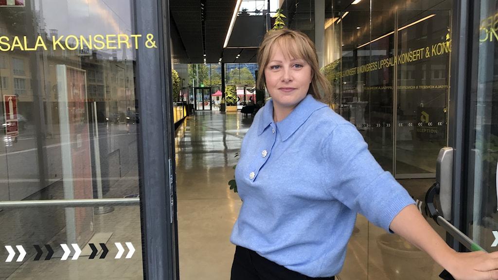 Ung kvinna i blå skjorta står i dörren till Uppsala Konsert och Kongress.