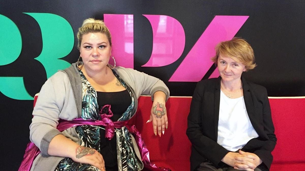Två blonda kvinnor sitter på en röd soffa och ler.