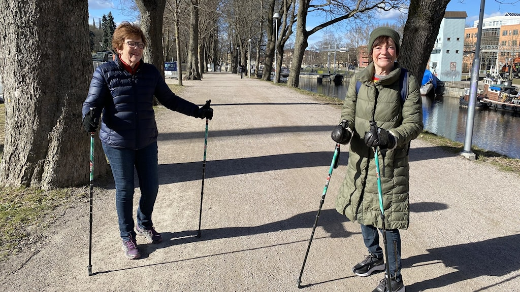 Två personer som promenerar längs Fyrisån i Uppsala med gåstavar.