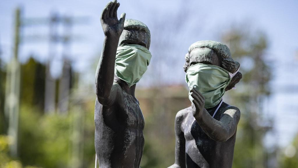 Två statyer förställande barn, bärandes munskydd.