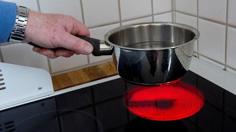 Någon kokar vatten i en kastrull på spisen.