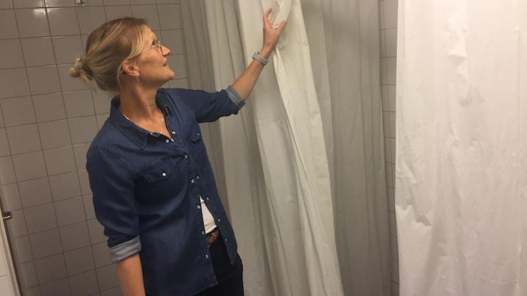 Läraren Jenny Eriksson visar upp draperierna som hänger i duschrummet på Harbo skola.