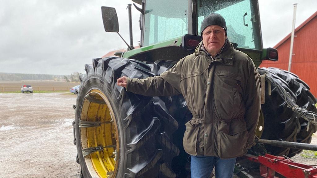 Kalle Grandin står bredvid sin traktor.