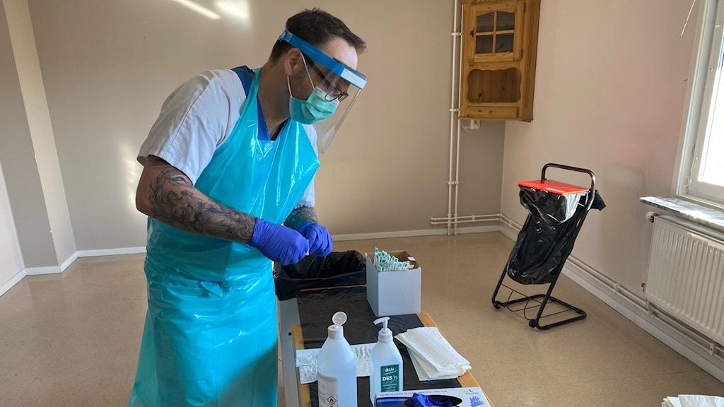 Provtagare Jimmy Wideberg har munskydd, visir, handskar och förkläde på sig och står lutad över provtagningsmaterial på ett bord.
