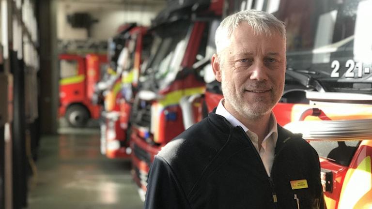 Avdelningschefen på Uppsala Brandförsbar har på sig en svart jacka, vit skjorta och står framför fyra parkerade brandbilar.