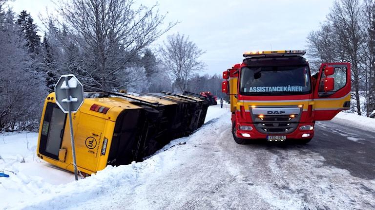 En gul buss har vält ner i diket och ligger på sidan. Bärgningsbilen står bredvid. Det är vinter och isig gata.