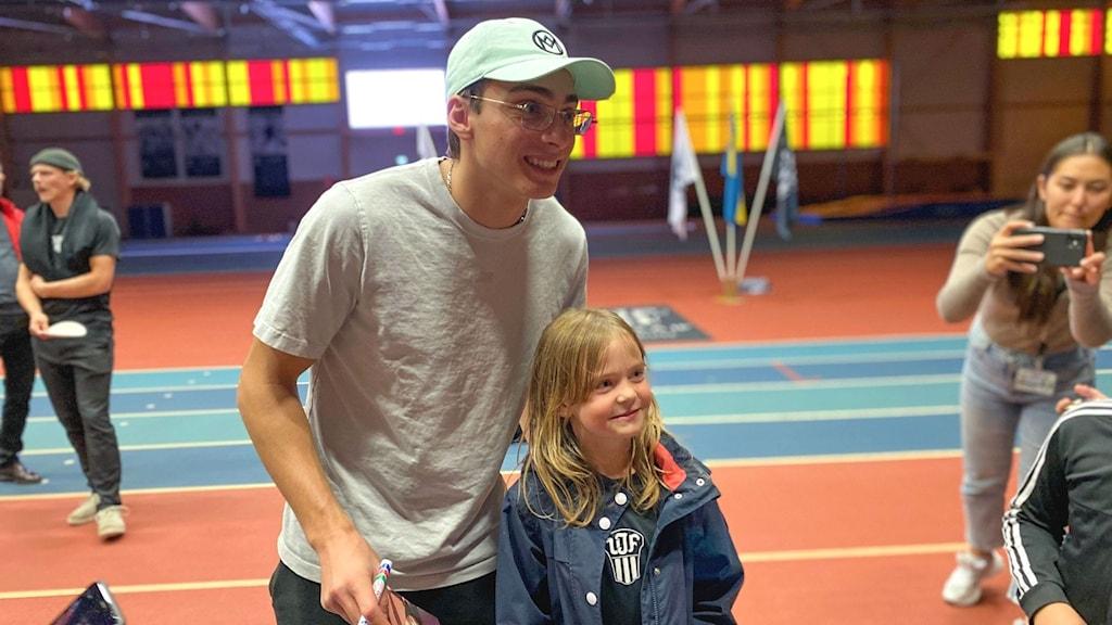 Armand Duplantis står bredvid ett barn i IFU Arena. Båda ler och poserar för en kamera.