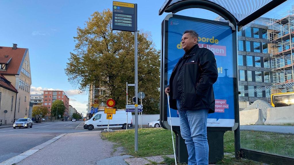 Man står vid busshållsplats och tittar ut mot bilvägen. I handen har han en vit blindkäpp.