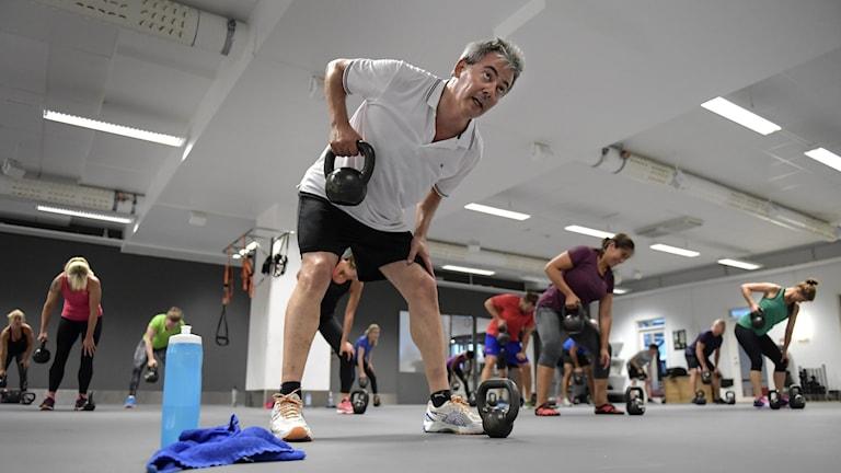 Ett tiotal personer står i en träningssal och styrketränar med kettlebells.