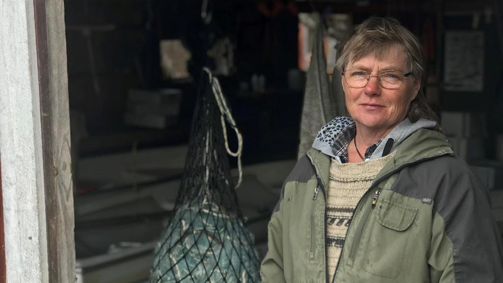 Mona Loberg står i en av båthusets öppningar och på sidan om henne hänger ett av hennes flera fisknät.